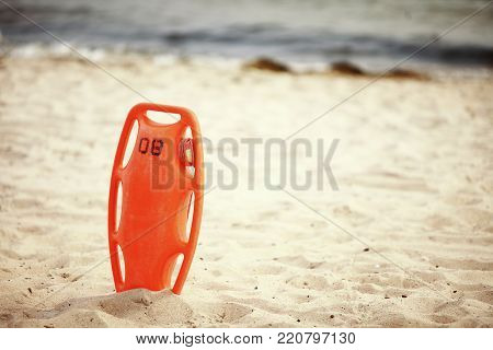 Beach life-saving. Lifeguard rescue equipment orange preserver tool, red plastic buoyancy aid in the sand