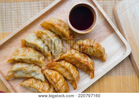 Japanese snacks of fried gyoza on wood tray