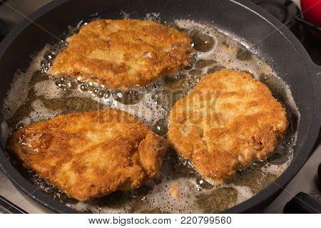 Frying wiener schnitzel in a hot pan with cooking oil