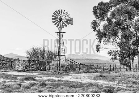 Monochrome water pumping windmill, dam and a kraal on a farm next to the road from Spoegrivier to Klipfontein in the Northern Cape Namaqualand region of South Africa
