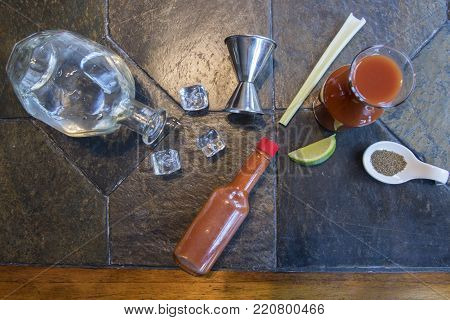 Bloody Mary or Caesar cocktail ingredients deconstructed on slate tabletop with ice cubes and shot glass with copy space,