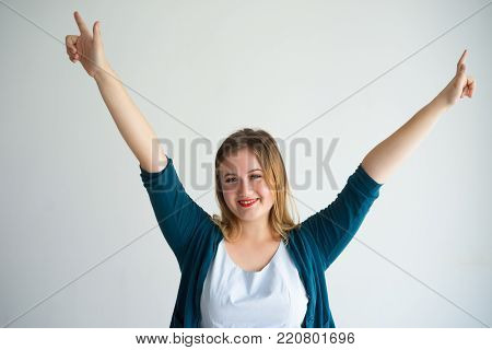 Closeup portrait of joyful young beautiful woman looking at camera, raising arms and celebrating success. Jubilation concept. Isolated front view on grey background.