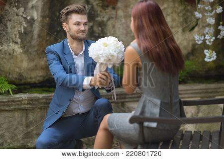 Young man Kneeling and giving bouquet of flowers to girlfriend in the garden.