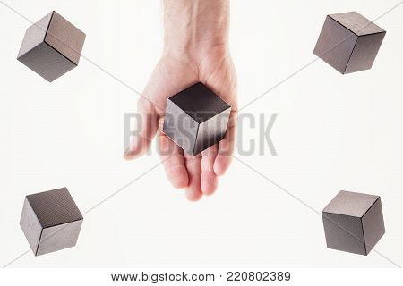 Black wooden cubes are floating. A man's hand takes a floating cube.  Concept of creative, logical thinking. Abstract background with cubes with copy space. Floating shapes.