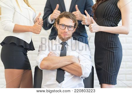 Crossing Arms and Smiling American man sitting While Group of Partner Showing Thumb Up over head. Like Concept.