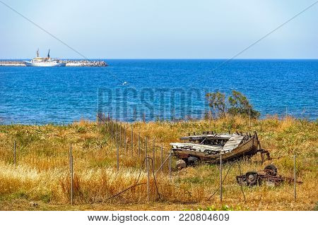 Old broken wooden boat on sea coast