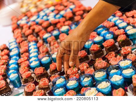 Pastry Shop with Colorful Tasty Cakes the confectioner reaches out his hand stock photo