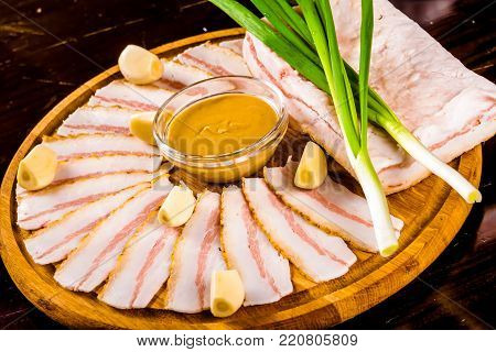 Ukrainian traditional food - salo. Sliced bacon with mustard, garlic, onion on wooden board