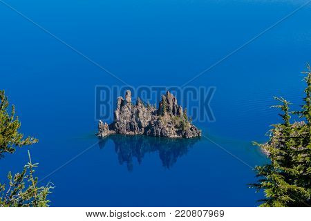 Phantom Ship Rock Through The Trees of Crater Lake on sunny day