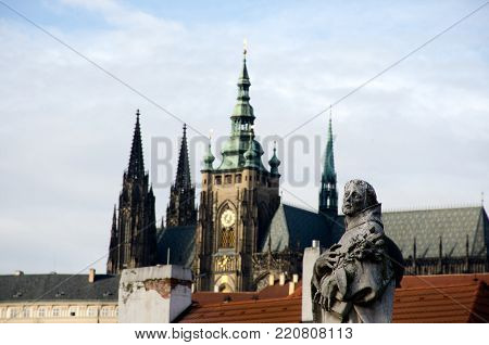 Statue on Charles Bridge with out of focus St Vitus Bridge in background