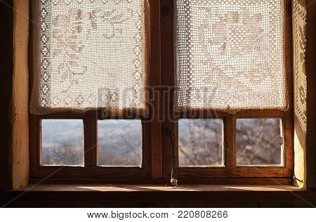 Details of the old Serbian household, a wooden window with embroidered curtains.
