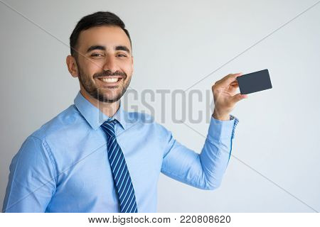 Closeup portrait of smiling young handsome man looking at camera and showing business card. Introduction concept. Isolated front view on grey background.