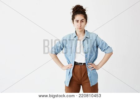 Portrait of young businesswoman with dark hair in bun wearing casual clothes, looking with annoyance, standing with hands on her hips, angry with her employees showing unsatisfactory results of work