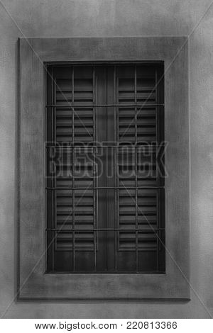 Closed window with old wood shutters, monochrome background