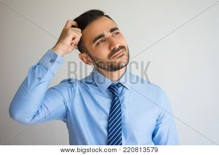 Closeup portrait of content young man scratching head in deep thoughts. Businessman thinking over attractive offer. Decision making concept