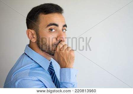 Portrait of pensive young man leaning head on hand and covering mouth with fist. Male manager thinking over new challenge. Business and challenge concept