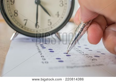 Students taking optical form of standardized exams near Alarm clock with hands holding yellow pen for final examination in school, college university classroom, Education concept