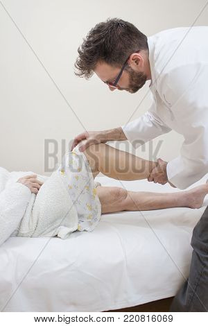 Orthopedist Doctor Examines The Knee Of An Old Woman Lying On A Bed.