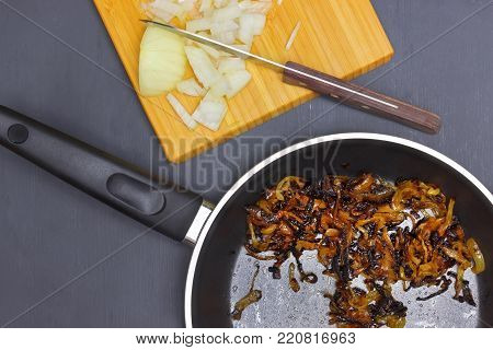 Onion disgusting leftovers. An overhead photo of burnt onion on the black teflon pan. Spoiled unhealthy overcooked burned meal. Messthetics aesthetic concept. Fried bad taste fat food for recycling