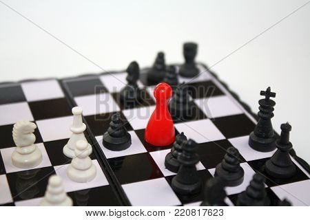 Red ludo figurine on chessboard with black and white chess pieces. Concept of unique unusual ideas, leadership, business topics.