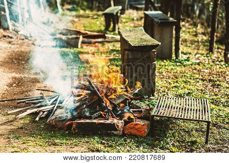 Burning fire for the the barbecue, part of a domestic garden, picnic details.