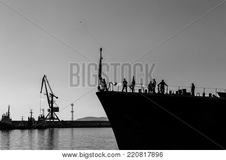 sailor throws a rope with the weight of the port observed by the other sailors of a military ship. a naval ship prepares to harbor a port in black and white.