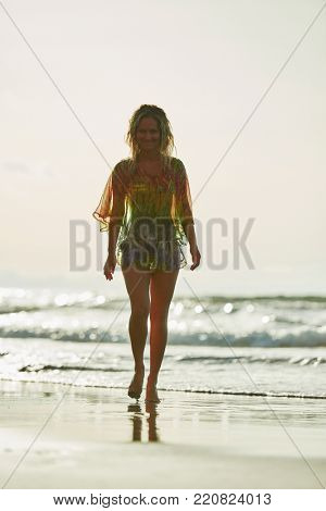 young caucasian woman refreshing on the beach in summer evening
