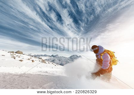 A professional snowboarder with a backpack leaves the cloud of snow powder at sunset against the background of epic clouds and a dark blue sky. Dynamic photo taken in motion. The concept of winter sports