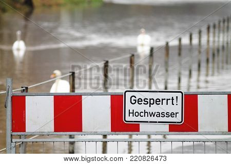 High water warning street barrier in germany. Spa town embankment under water. High water warning sign, red and white flood barrier.