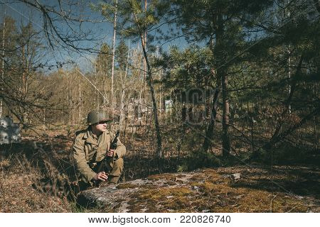 Gomel, Belarus - April 23, 2017: Re-enactor Dressed As Soldier Of USA Infantry Of World War II Hidden Sitting With Thompson Sub-machine Gun In Forest Ambush At Historical Reenactment