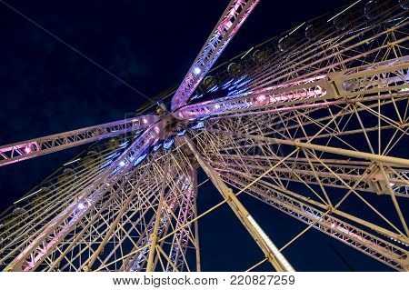Night view of huge illuminated construction of huge ferris wheel against dark blue sky in Marseille, France
