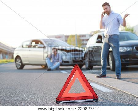 Man calling first aid after a bad car crash on the road