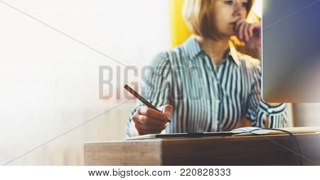 graphic designer working at office with digital stylus on background monitor computer at night, hipster manager using device pen, female hands graw on portable tablet, work process concept in workplace