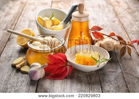 Composition with honey and garlic as natural cold remedies on wooden background