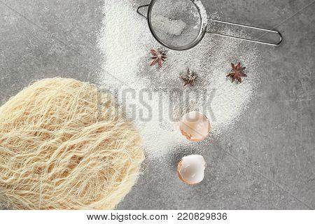 Shredded thin dough with sieve on table