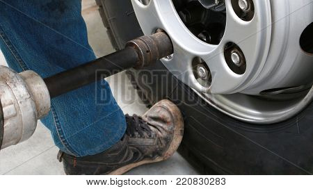 Asian Man Machanic Changing A Wheel Of A Car Truck In Workshop. Mechanic Changing Truck Wheel In Aut