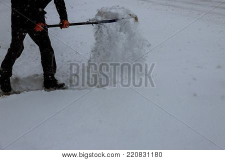Man with snow shovel cleans sidewalks in winter. Winter time. Man Removing Snow with a Shovel
