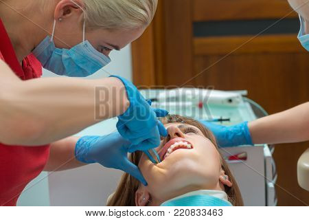 Close-up woman with ceramic braces on teeth at the dental office. Dentist holding dental tool - corner ligature cutters. Orthodontic Treatment. Process of installation of braces