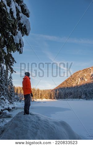 Man in orange jacket on small hill looking to frozen lake Fusine and sun covert forest poster