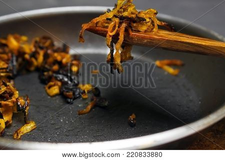 A photo of burnt onion on the teflon pan and wooden spatula. Spoiled unhealthy overcooked burned meal. Onion disgusting leftovers. Messthetics aesthetic concept. Fried bad taste fat food for recycling