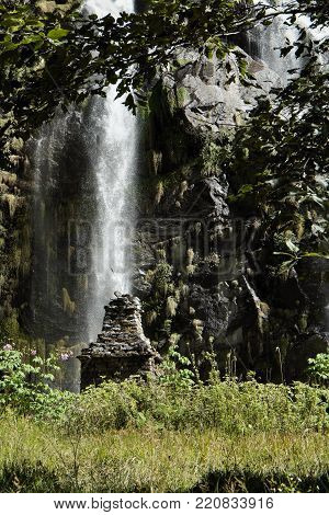 Waterfall in the mountains in Nepal among green plants with old buddist chorten monument