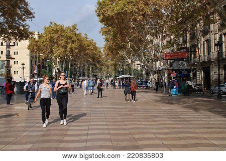 BARCELONA, SPAIN - NOVEMBER 2, 2017: People walk on the tree lined La Rambla. The pedestrianised avenue is a popular tourist destination.