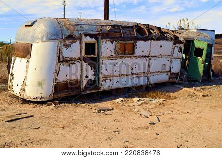 Forgotten haunting landscape including a dilapidated trailer on a dusty plain taken at a ghost town in the desert