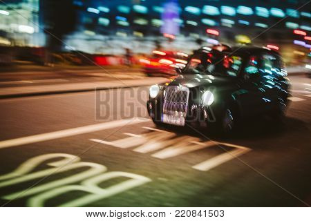 Abstract defocused in motion British Taxi hackney carriage cab driving fast to destination on the London street at night - transportation business theme with defocused motion on Bus lane and bokeh