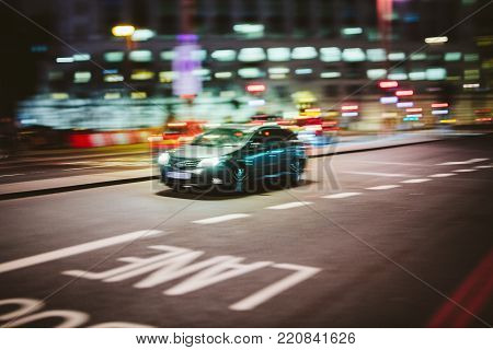 Abstract defocused in motion British car driving fast to destination on the London street at night - transportation business theme with defocused motion on Bus lane and bokeh