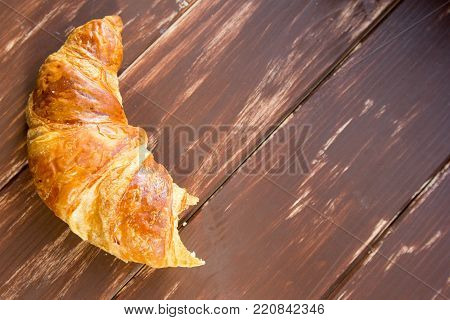 Fresh french bitten croissant at brown wooden background