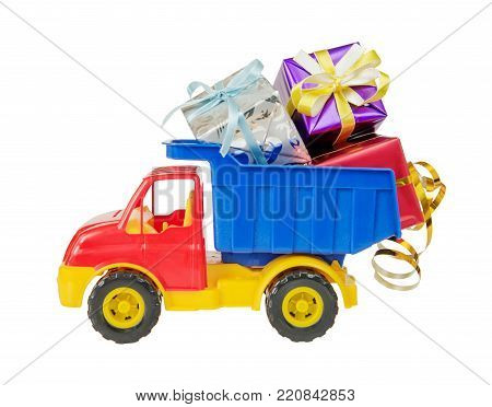 Multicolored plastic toy lorry delivers many gift boxes tied with decorative ribbons in body,  isolated on white background