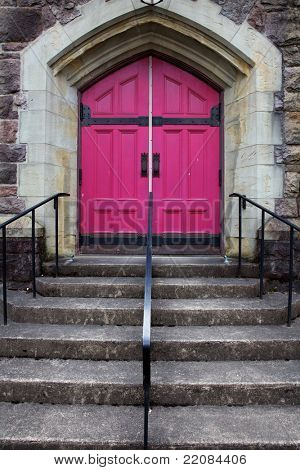 Steps leading to the double Fuschia  Doors of a Catholic church with a stone triangle feature