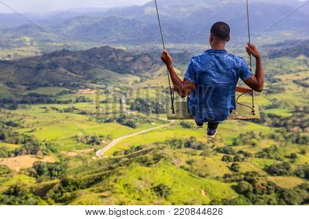 Flying at the wooden swing above the mountains. Nature landscape. Dominican Republic