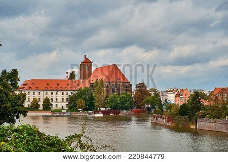 Wroclaw Old Town. Cathedral Island (Ostrow Tumski) is the oldest part of the city at the sunset. Blessed Virgin Mary Church on Odra River Island Piasek and Odra Tumski bridge (Tumski Most)